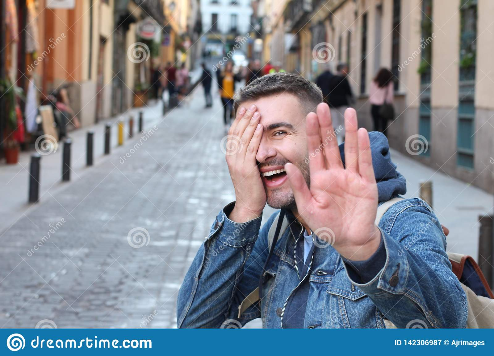 Shy man covering his face while smiling