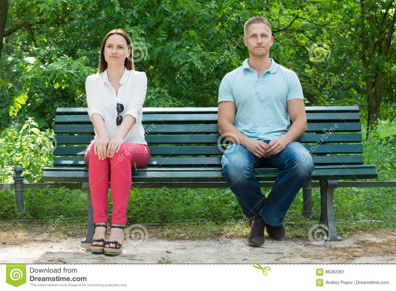 Shy Man And Woman Sitting On Bench