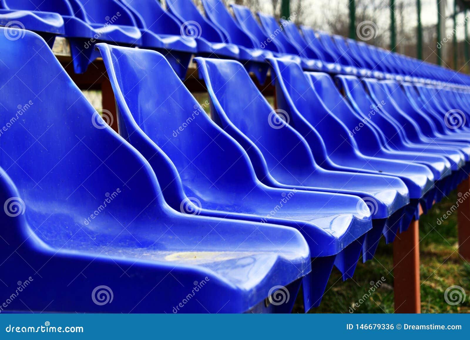 Sièges vides de bleus sur l au sol de sports en plein air