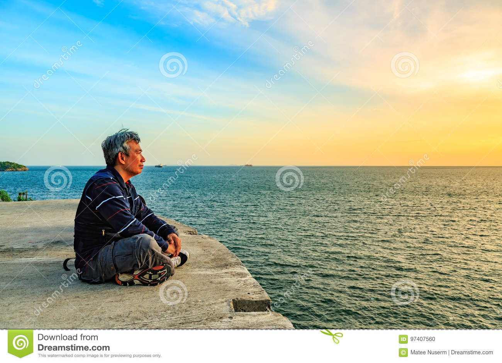 Siéntese y mirando a la puesta del sol