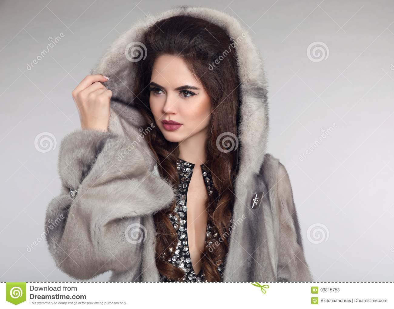 Siberian woman in mink fur coat over studio gray background. Fashion brunette girl with cowl.