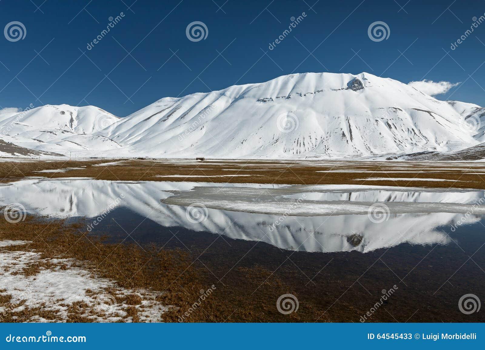 Sibillinibergen in het water met sneeuw worden weerspiegeld die