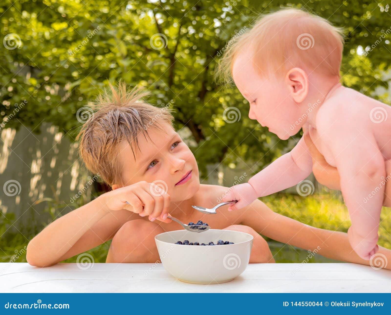 Sibings die verse sappige bessen eten Gelukkig kinderjarenconcept Gezond voedsel Gezondheidszorg van kinderen Peuter het eten