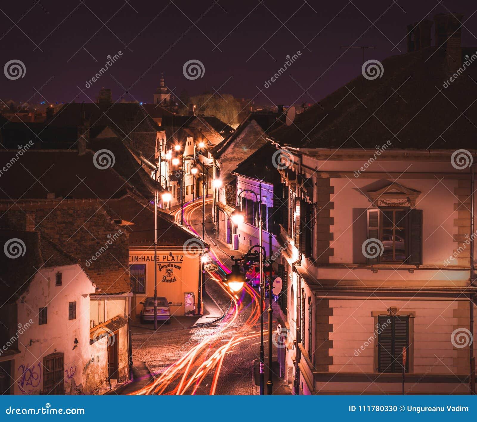 SIBIU, ROMANIA - 13 FEBRUARY 2016: SBeautiful downtown street with car lights in Sibiu, Romania.