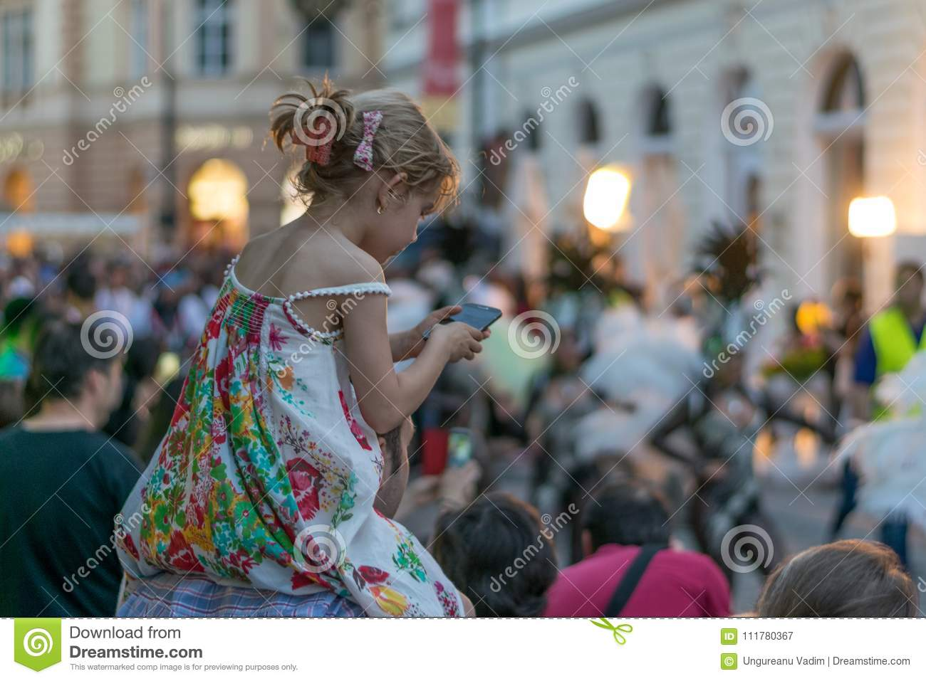 SIBIU, ROMANIA - 17 JUNE 2016: A girl is checking the phone while some carnaval dances are going on, during Sibiu International Th