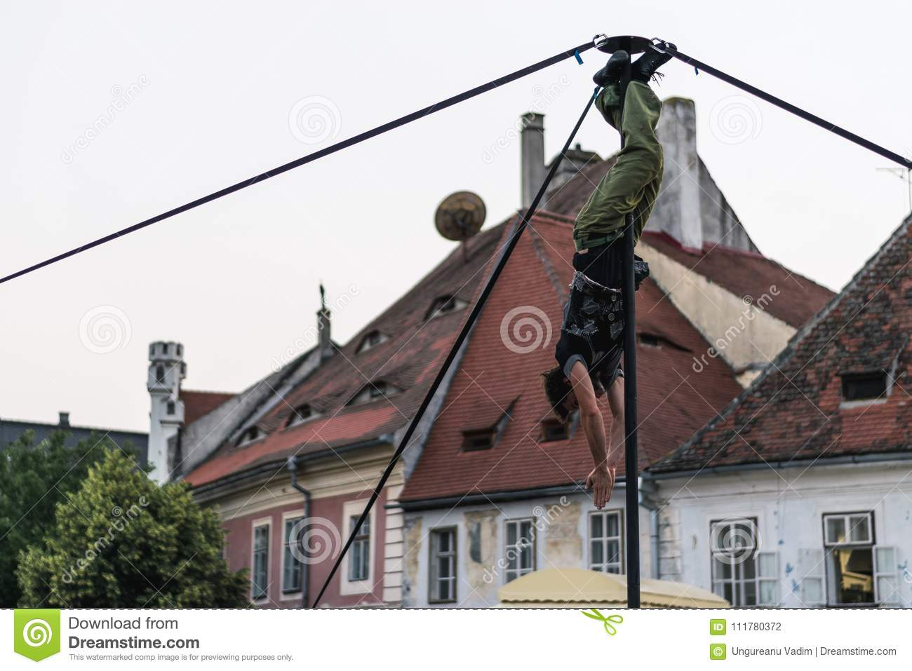 SIBIU, ROMANIA - 17 JUNE 2016: A member of Kinemtatos, Manoamano Circo, Argentina performing a trick on the metal bar in the Littl