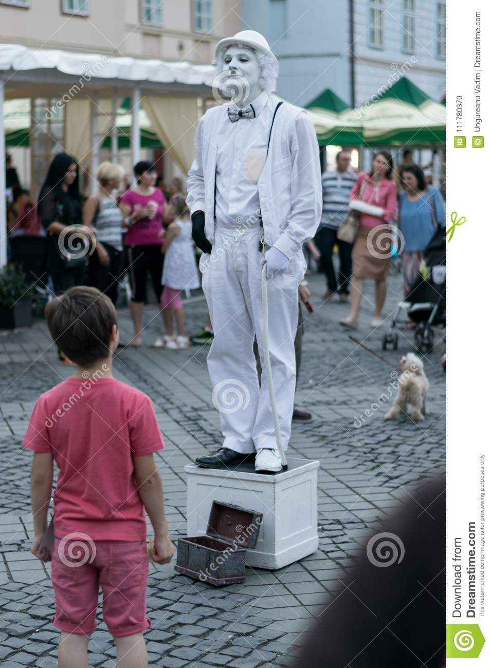 SIBIU, ROMANIA - 17 JUNE 2016: A mime has caught the attention of a boy,in Big Square during Sibiu International Theatre Festival,