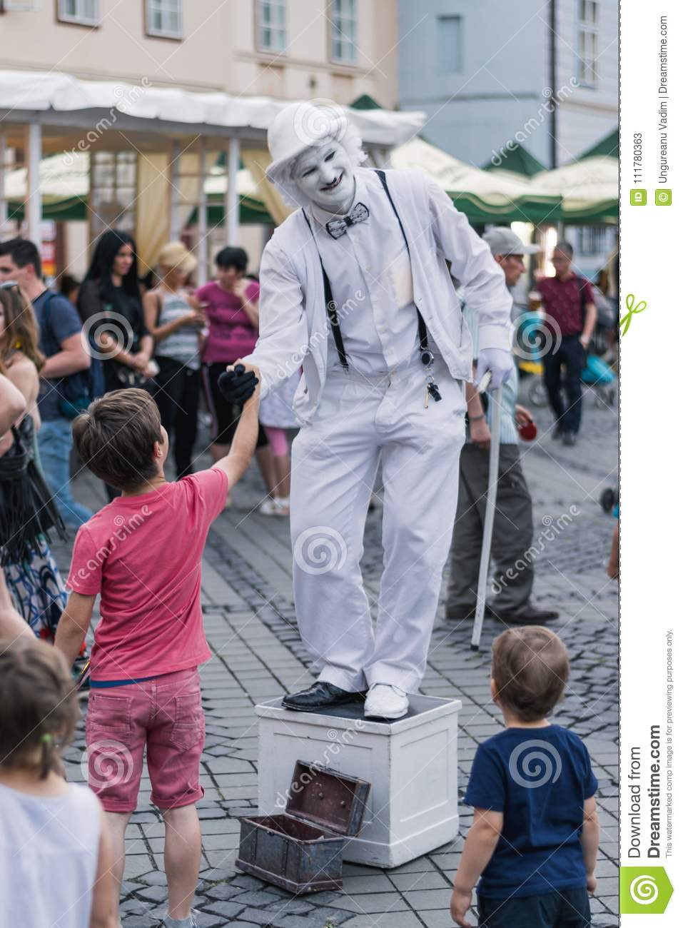 SIBIU, ROMANIA - 17 JUNE 2016: A mime is shaking hands with a boy in Big Square during Sibiu International Theatre Festival, Sibiu