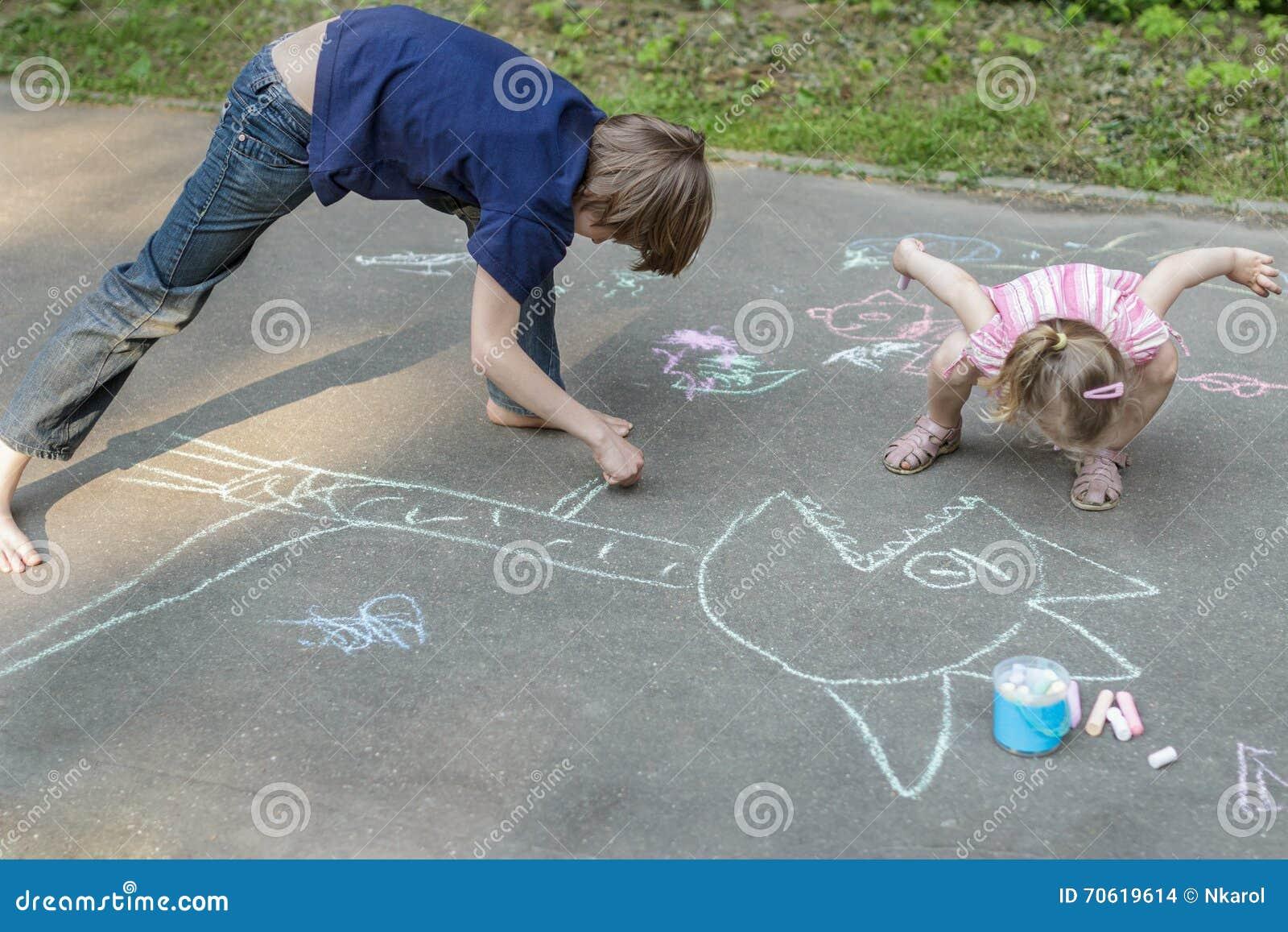 Siblingbarn som spelar under trottoaren som chalking på asfaltyttersida