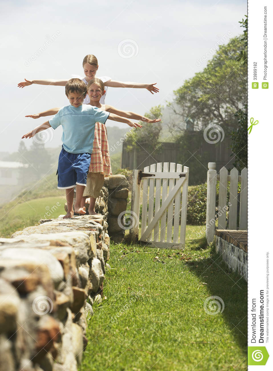 Siblings Balancing While Walking In A Row On Stone Wall