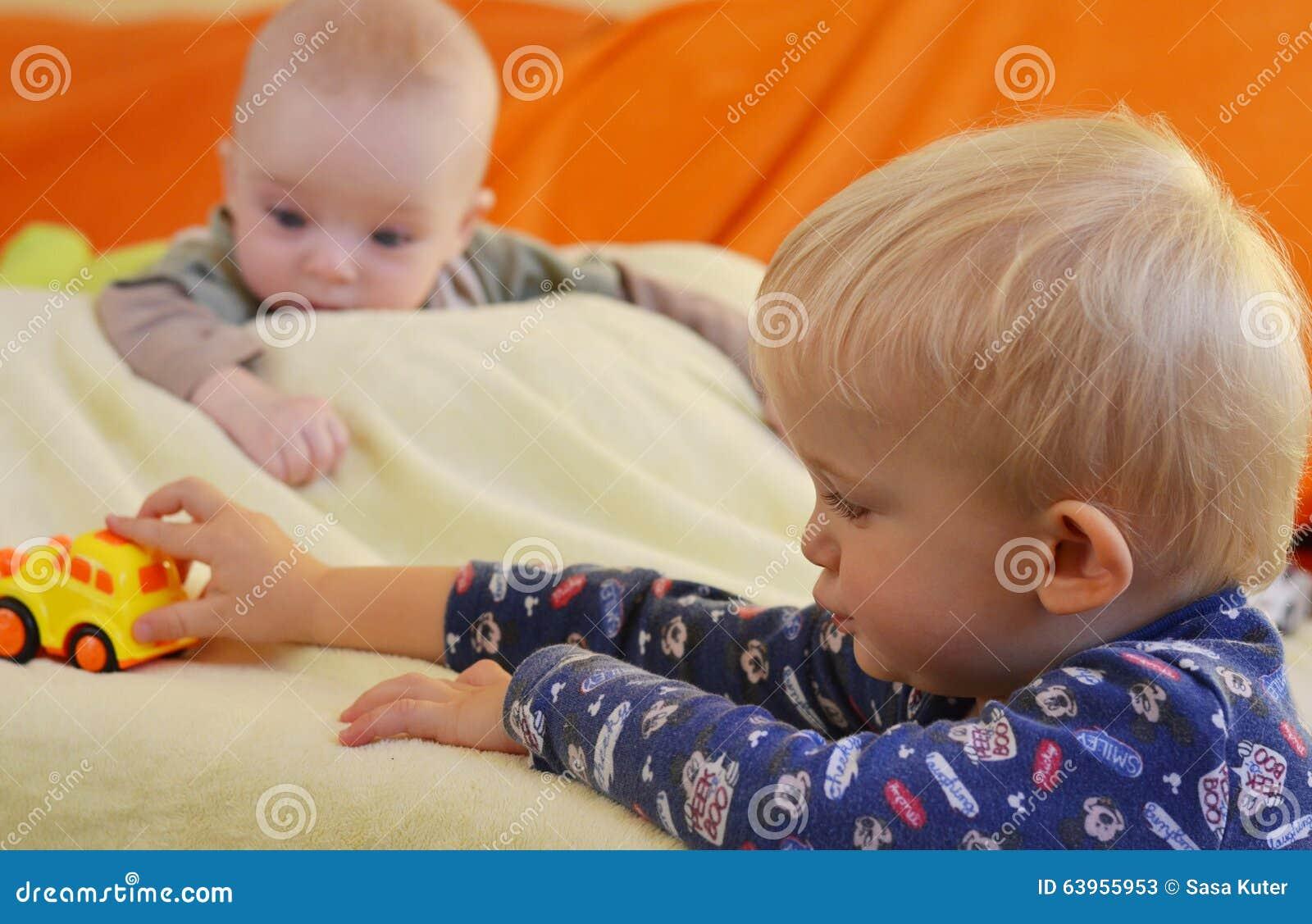 Toys For Siblings : Siblings enjoy of toys baby is watching older brother