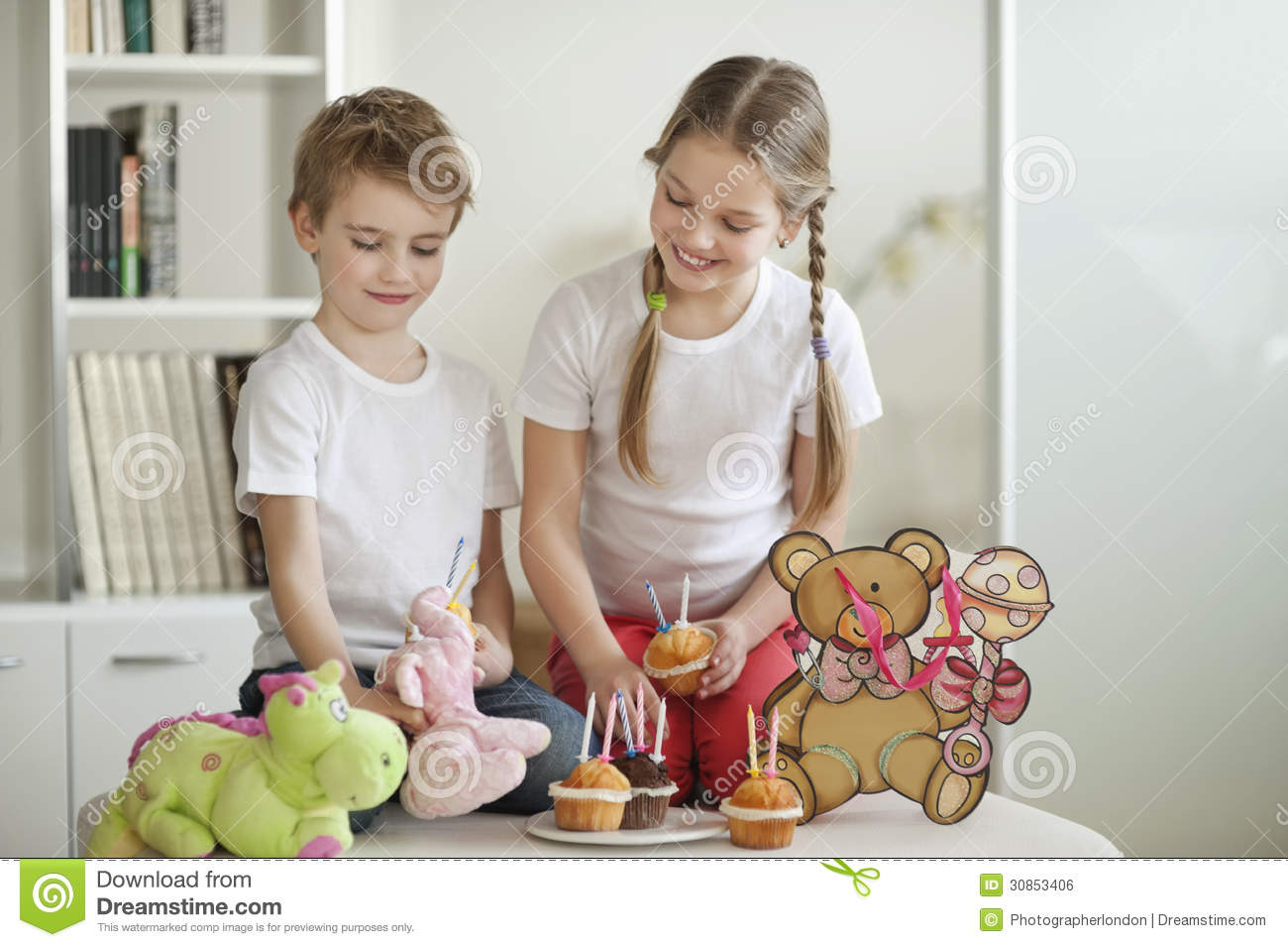 Toys For Siblings : Siblings and soft toys celebrating birthday with cup cakes