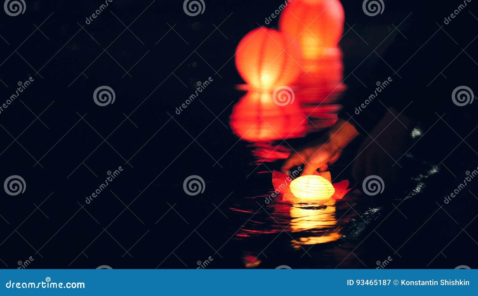 Sich hin- und herbewegende Beleuchtung Laternen auf Fluss nachts beleuchten - romantisches Festival