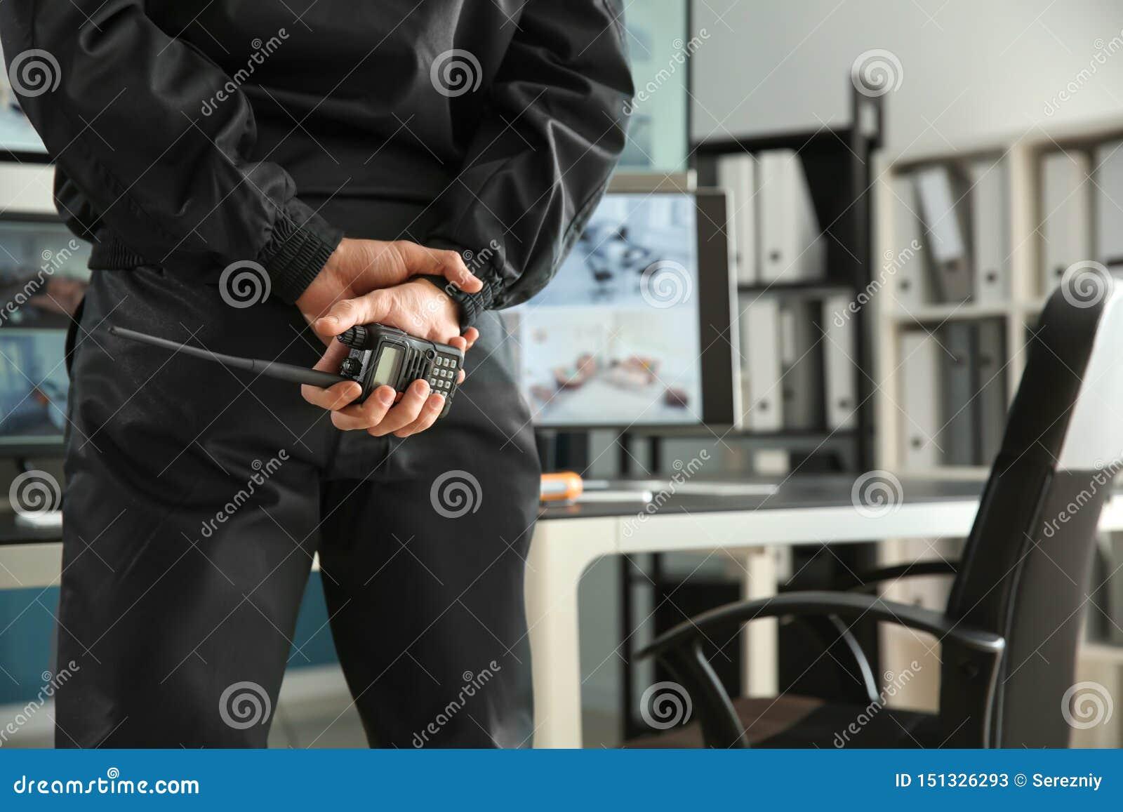 Sicherheitsbeamte mit dem Übermittler des portablen Radios, der moderne Überwachungskameras im Überwachungsraum überwacht