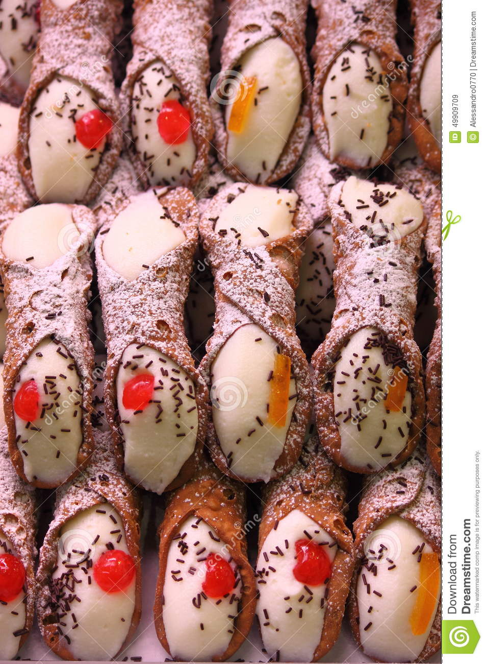 Pile of sicilian cannoli filled with ricotta and chocolate chips.