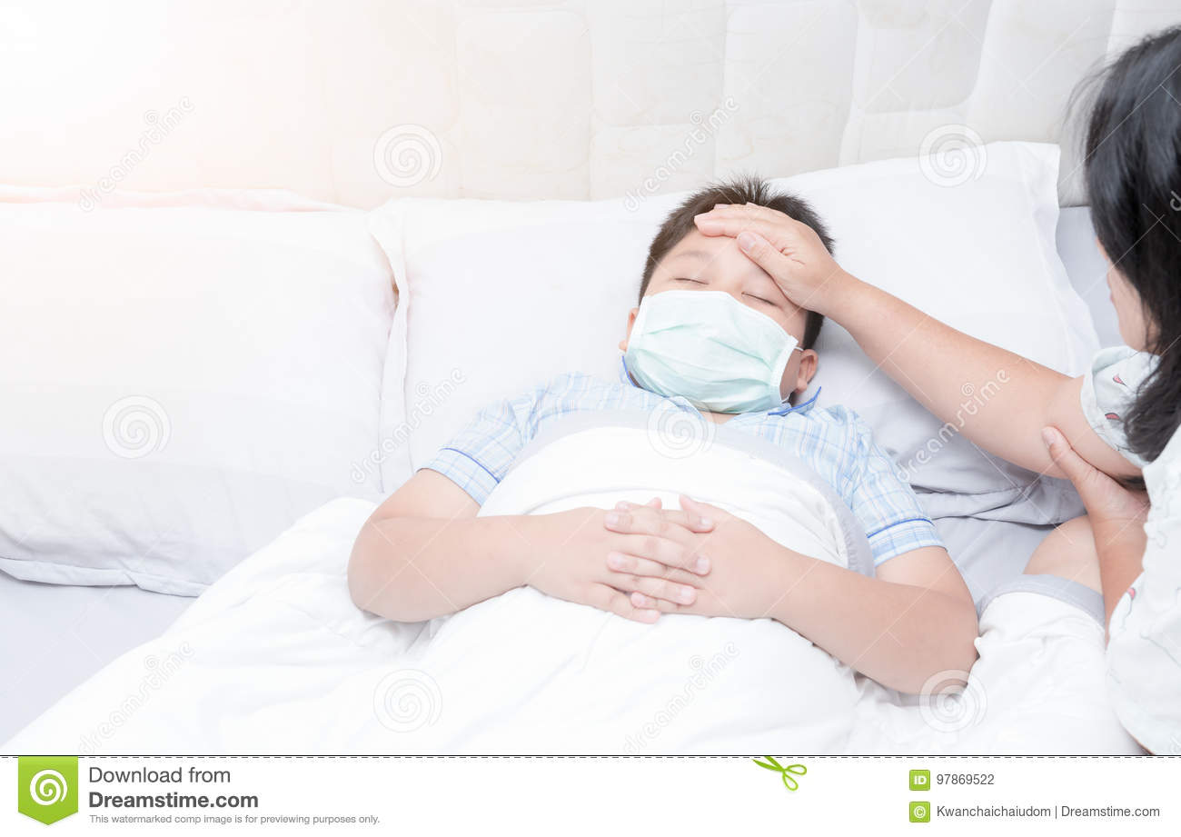 Sick boy with hygienic mask laying on bed