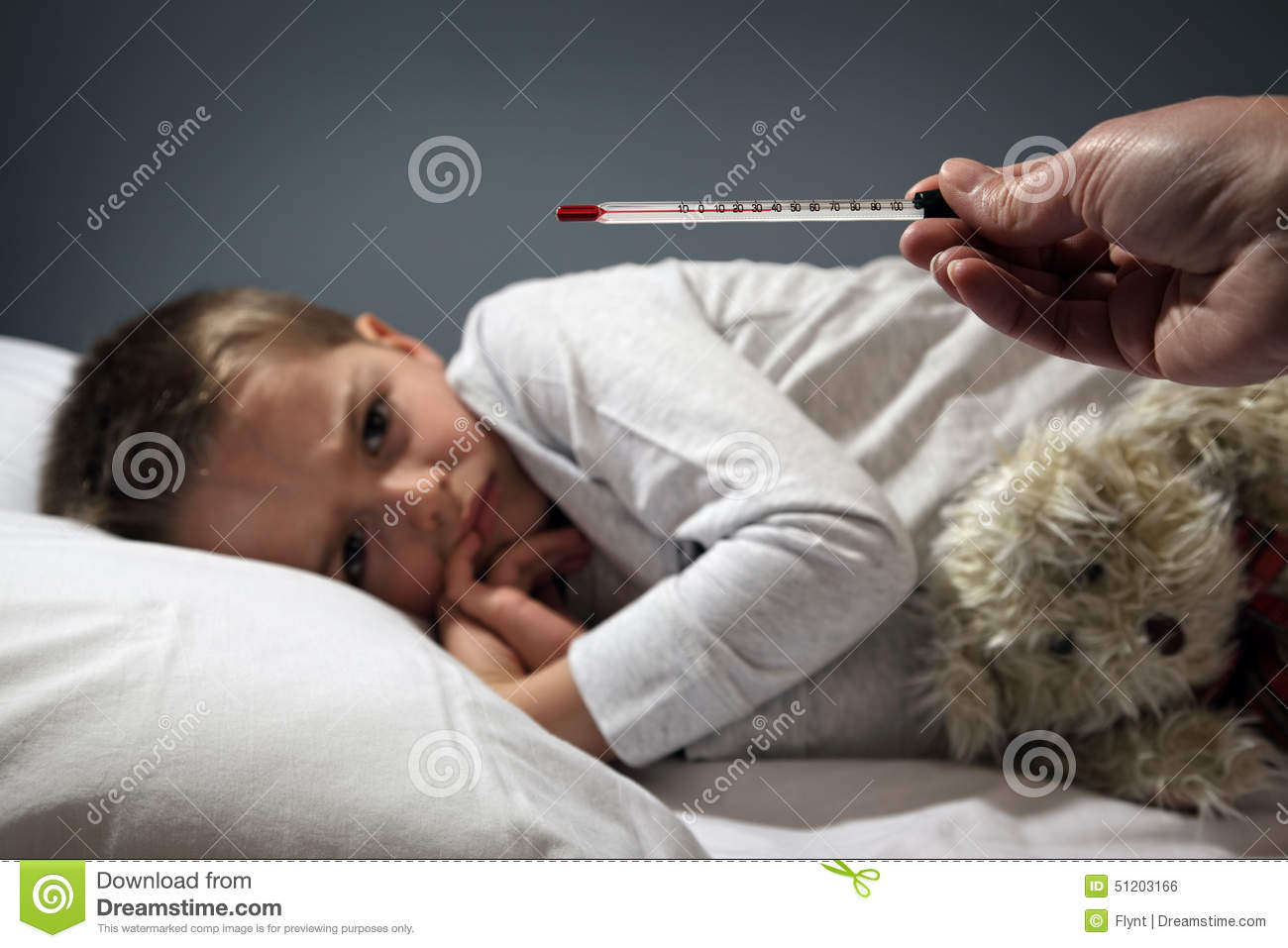 Sick Child In Bed With High Temperature Stock Photo