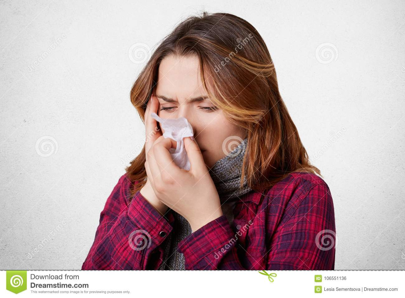 Sick desperate woman has flu, running nose, blows nose in handkerchief, has terrible headache, caught cold after long walk outside