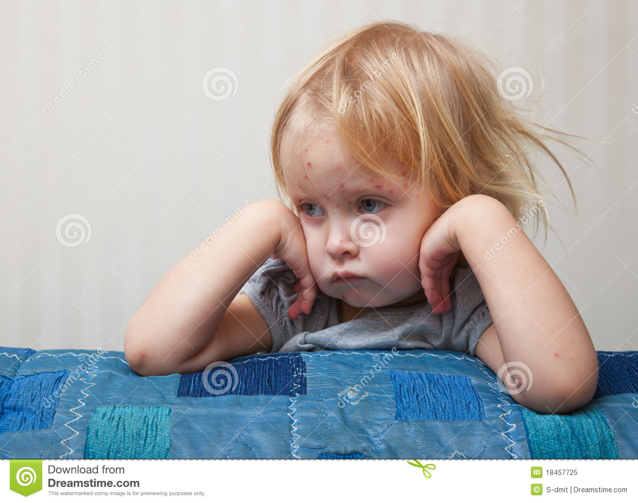 A sick girl is sitting near the bed