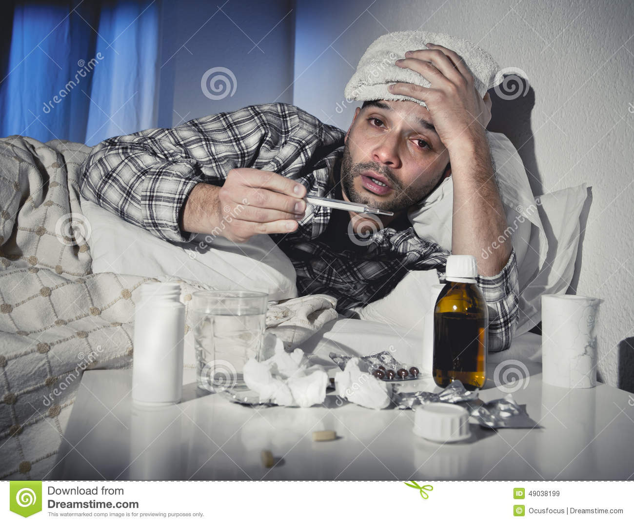 Sick man lying in bed suffering cold and winter flu virus having medicine and tablets