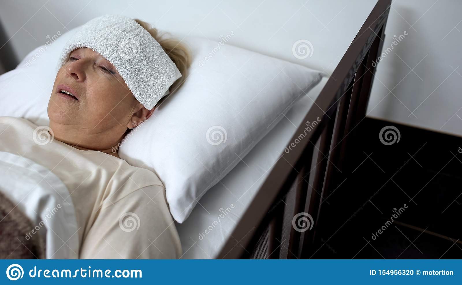 Sick Mature Woman Lying In Hospital Bed With Compress On
