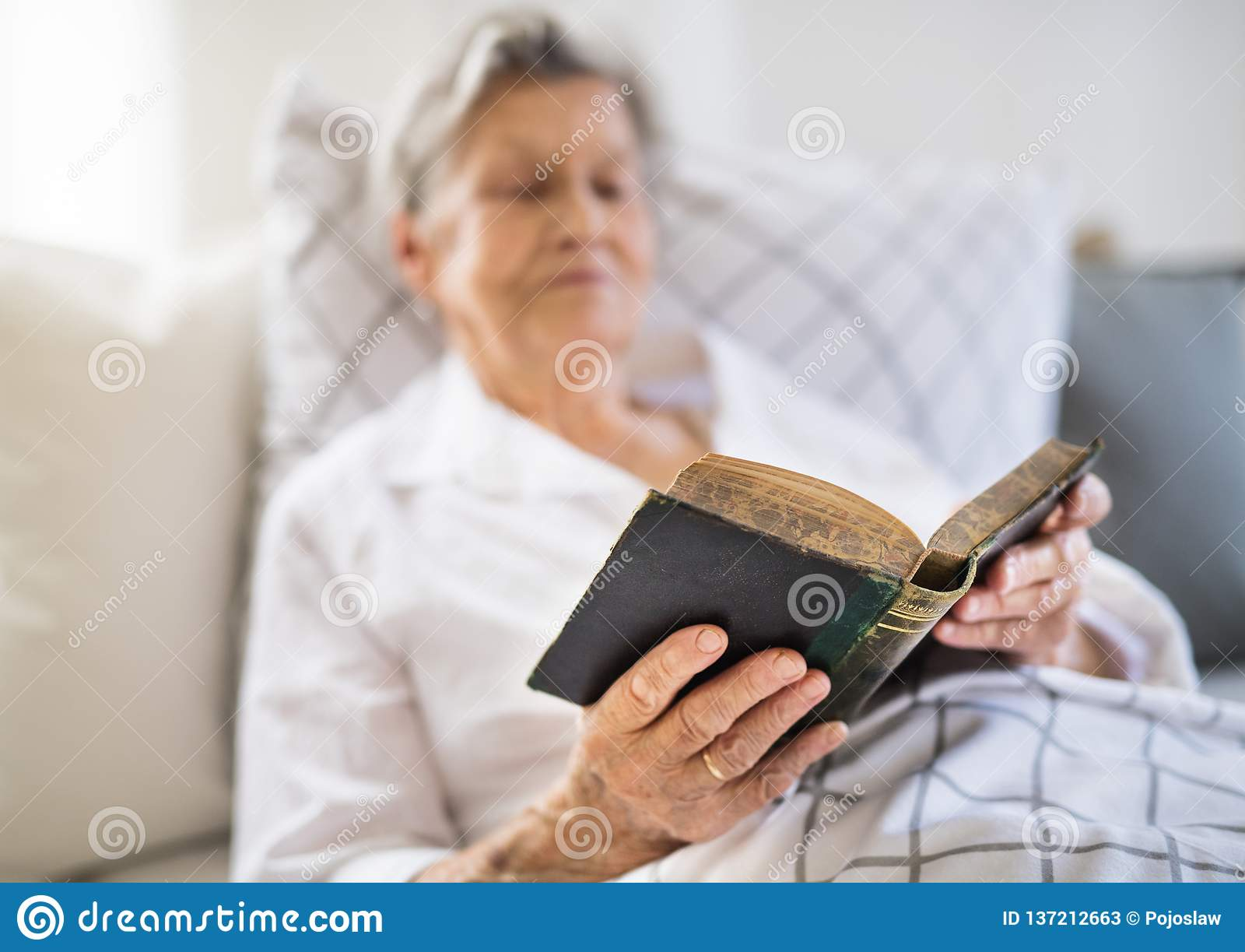 Sick Senior Woman Reading Bible Book In Bed At Home Or In