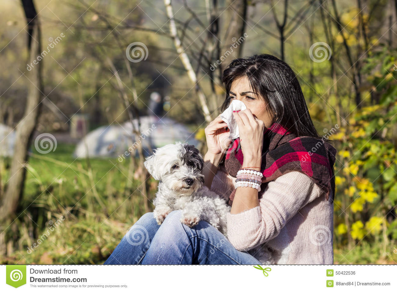 Sick woman relaxing in the autumn park with her dog