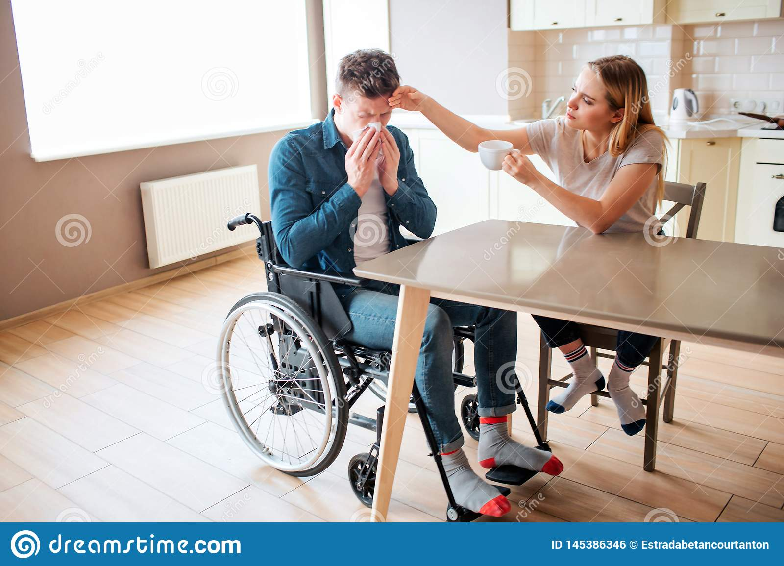 Sick young man with special needs and disability sneezing. Sick and ill guy. Young woman sit beside in kitchen and take
