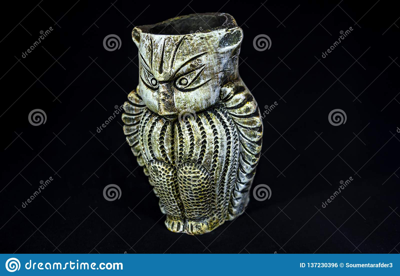 Side Angle View Of Terracotta Owl.Made out of clay with selective focus and isolated black background.