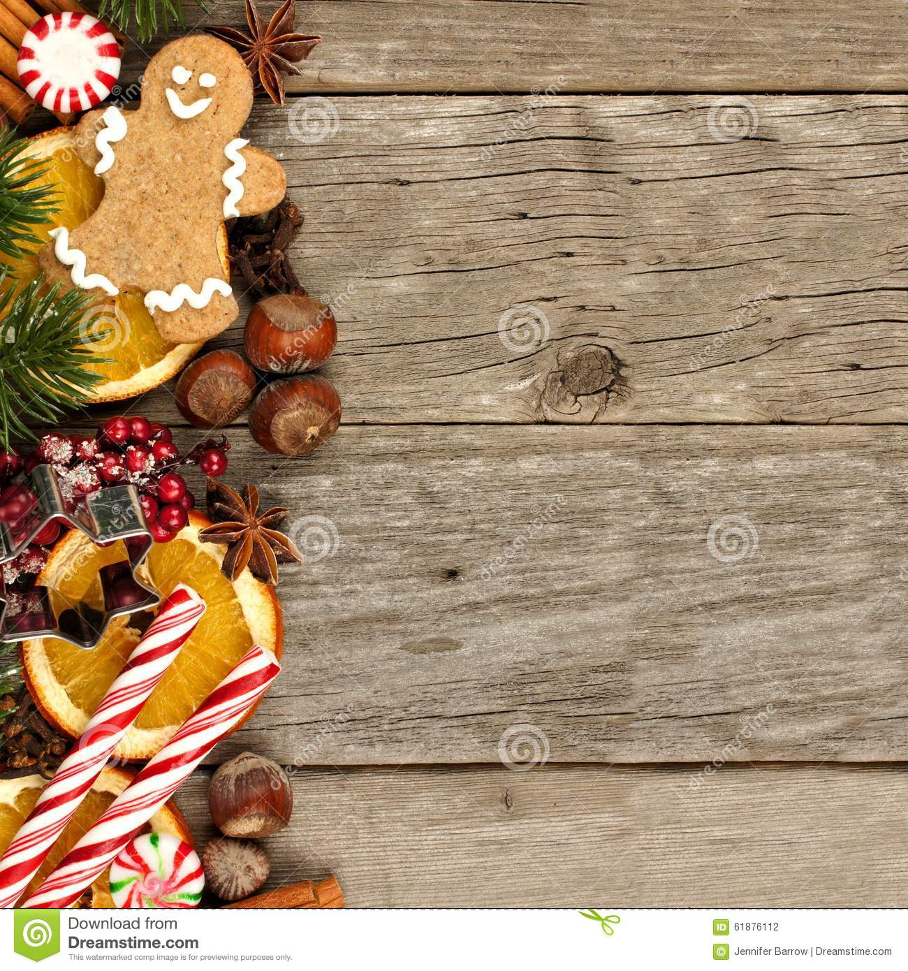 Side border of Christmas decor and treats over rustic wood