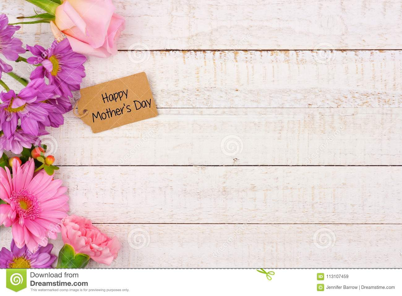 side border of flowers with mothers day gift tag against white wood