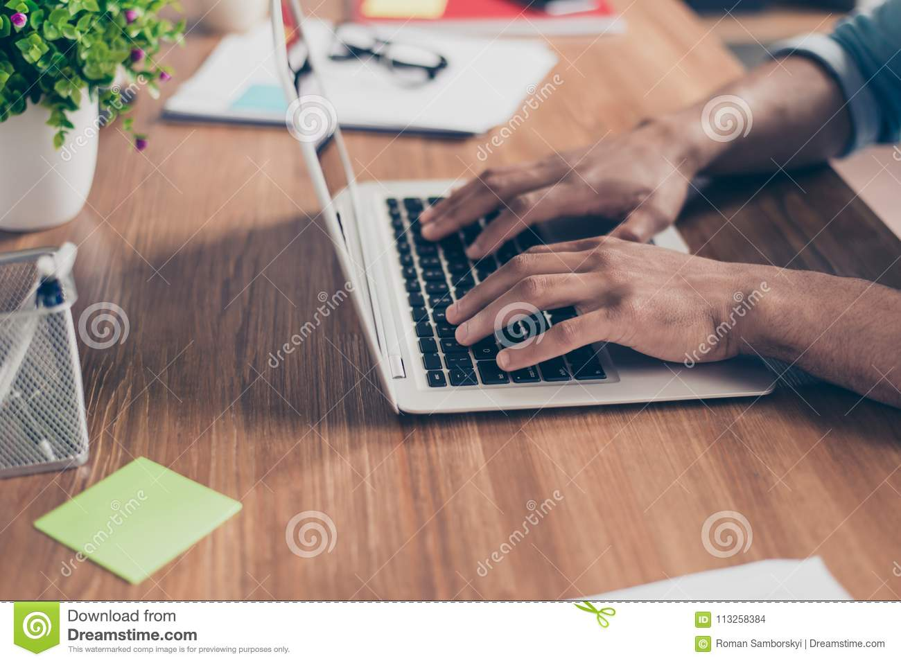 Side profile cropped photo of afro american`s businessman hands on keyboard of laptop on a wooden desk top, busy typing the data