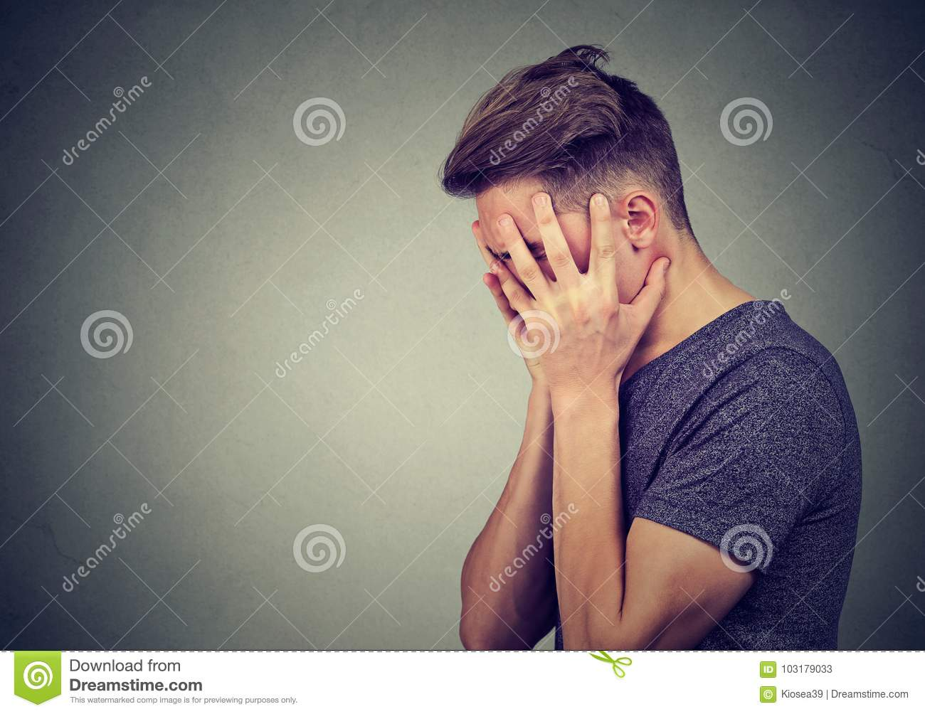 Side profile of a sad young man with hands on face looking down. Depression and anxiety disorder