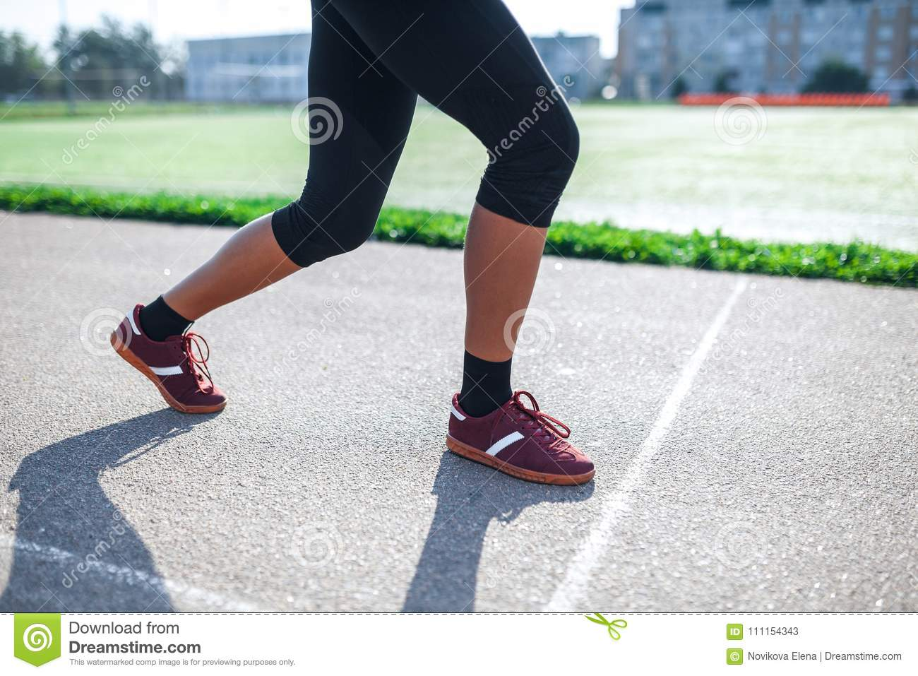 Side view Athletic woman on running track getting ready to start run,  Amateur athlete. Close up legs.