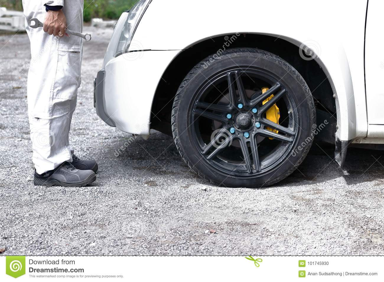 Side view of automotive mechanic man in white uniform holding wrench in his hands ready to repairing car engine.