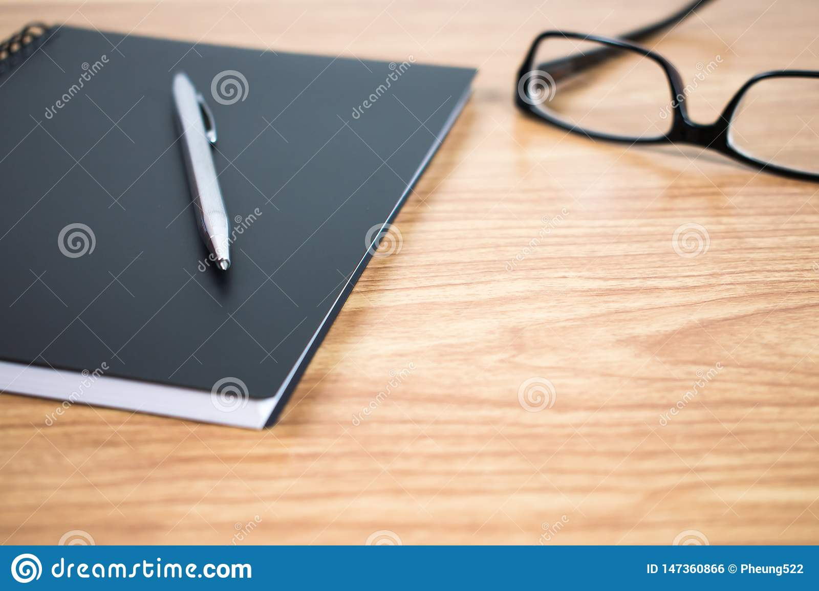 Side view of a pen and notebook at the ready on the table. Close up.