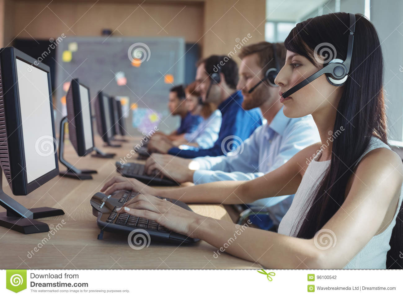 Side view of businesswoman typing on keyboard at call center