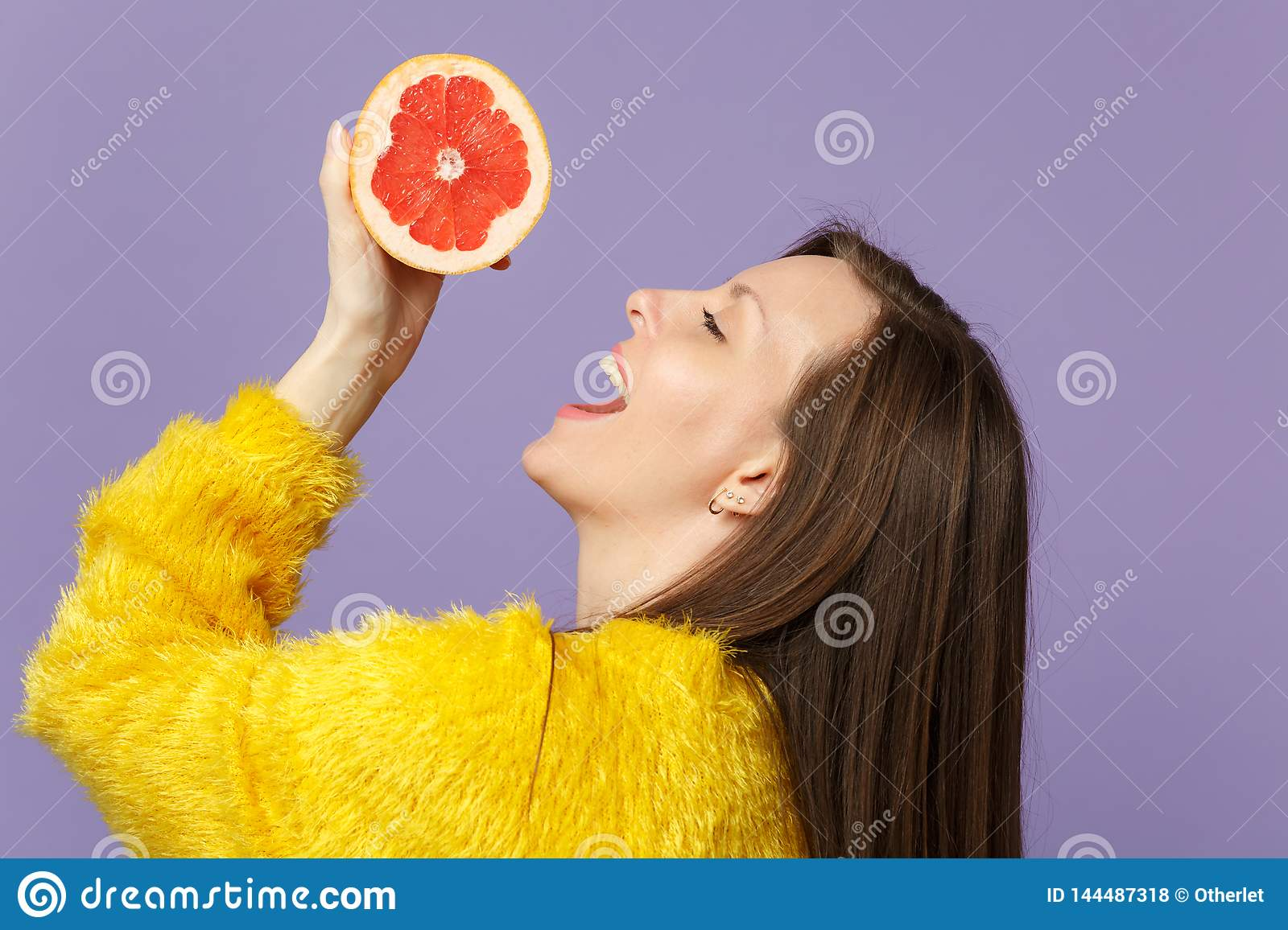 Side view of cheerful young woman in fur sweater holding in hand half of fresh ripe grapefruit isolated on violet pastel