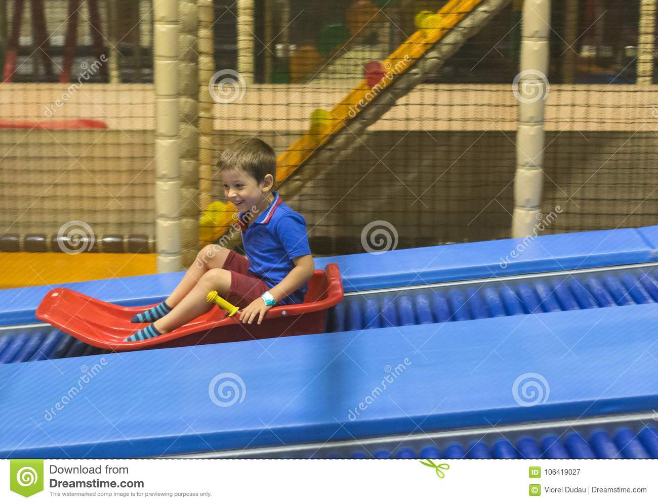 Child on slide ride in play area
