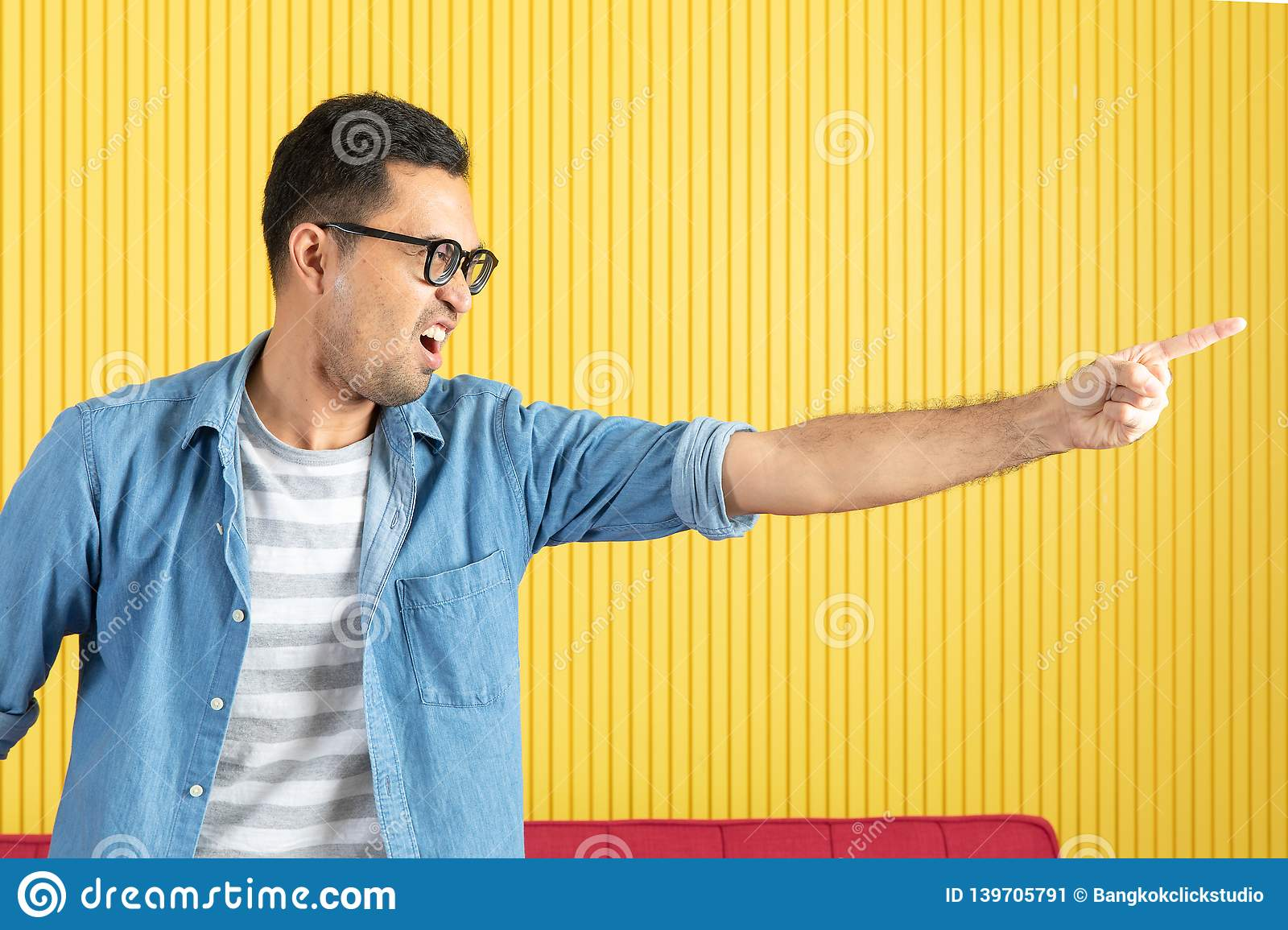 Side-view, close up of young Asian handsome bearded man, wearing eyeglasses, in denim shirt, pointing playfully to his left side,