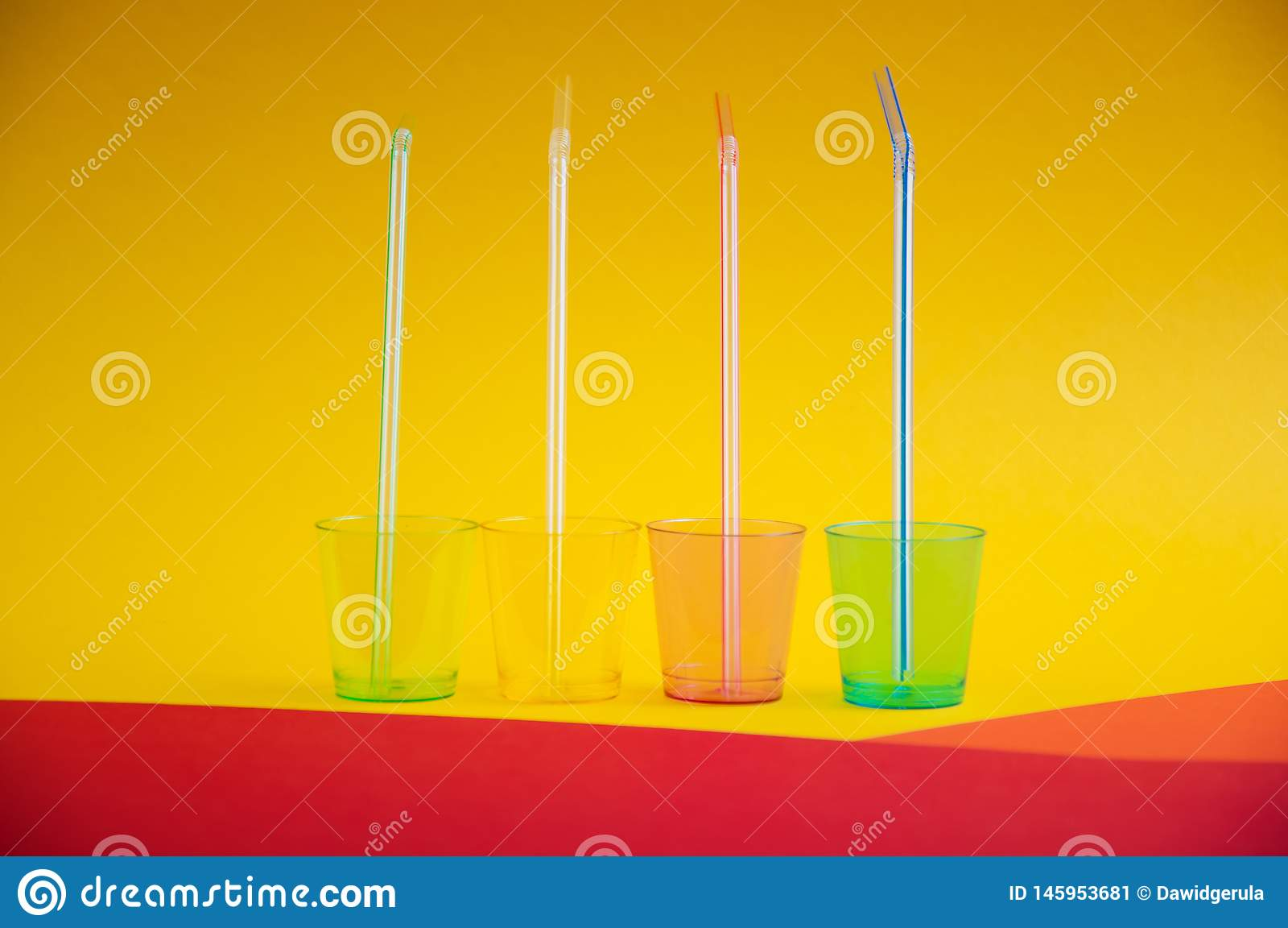 Side view of colorful empty plastic glasses with straws inside them, on multi color background