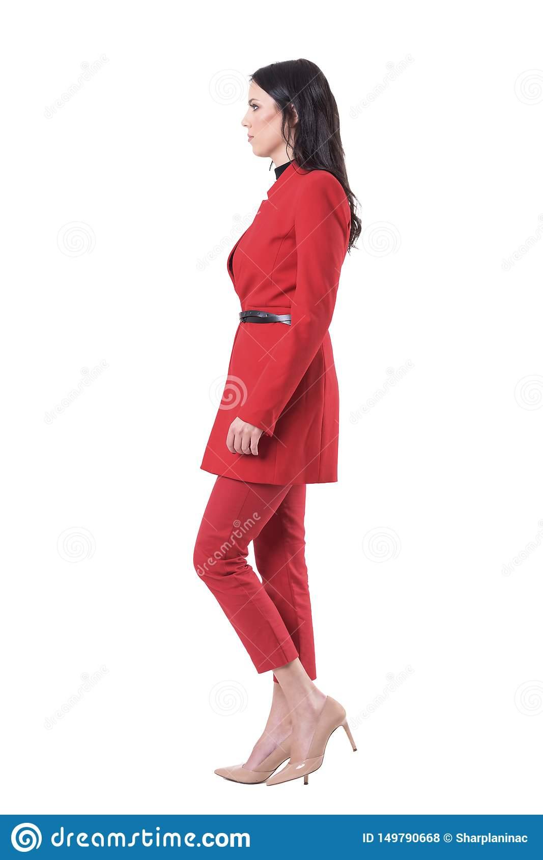 Side view of confident serious business woman in red suit walking and looking ahead.