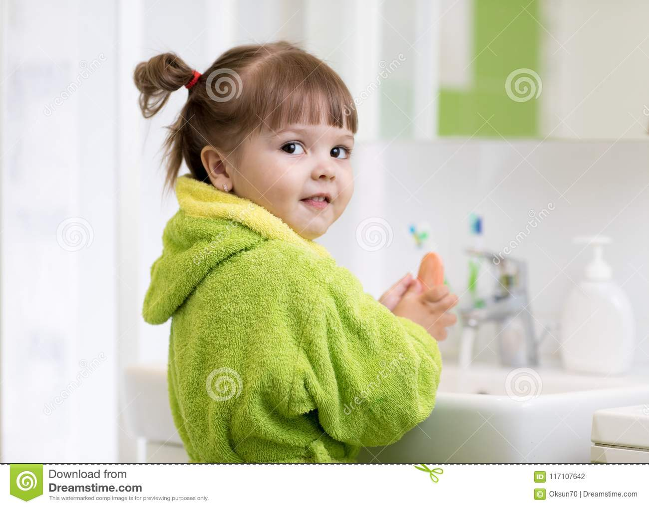 Side view of cute little girl in green bathrobe washing her hands.
