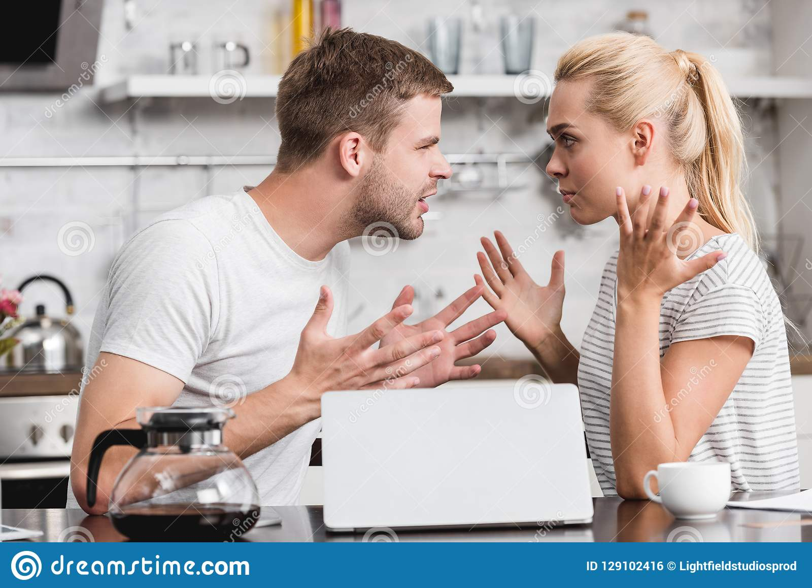 side view of emotional young couple arguing and looking at each other in kitchen relationship difficulties