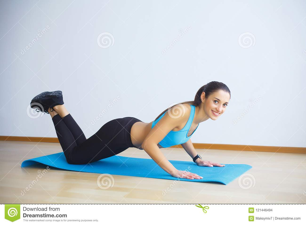 Side view of fit woman doing plank core exercise