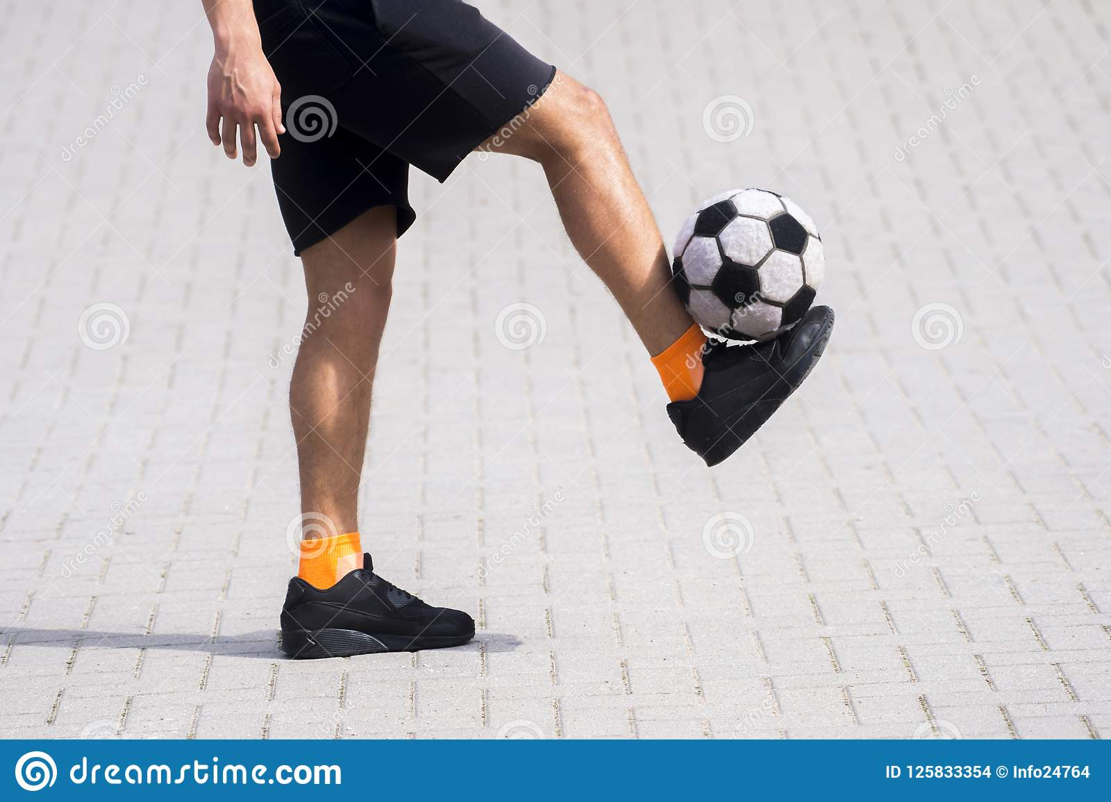Side view of freestyle soccer or futsal player juggling ball wit