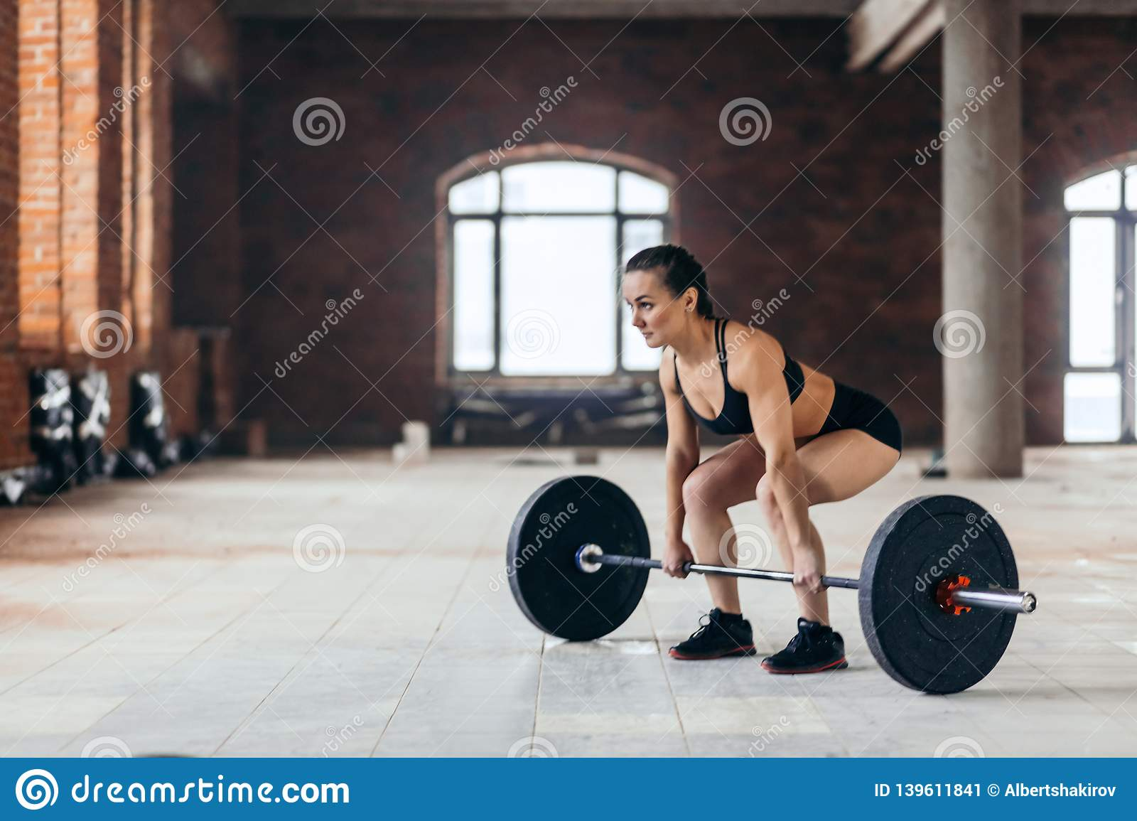 Side view full length photo of rslim strong girl working out with a barbell