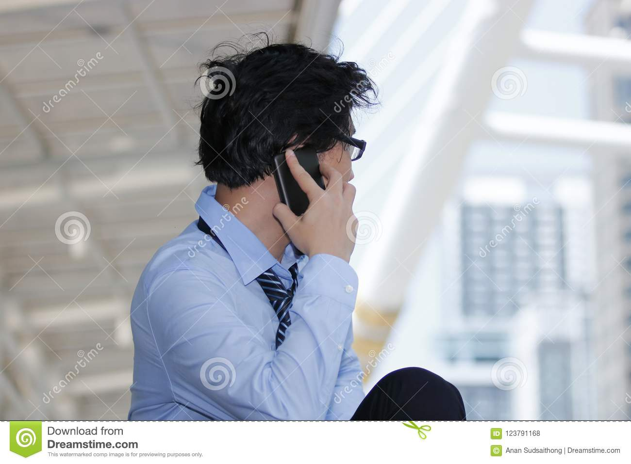 Side view of handsome young Asian businessman talking mobile smart phone at urban building background. Unemployment business conce