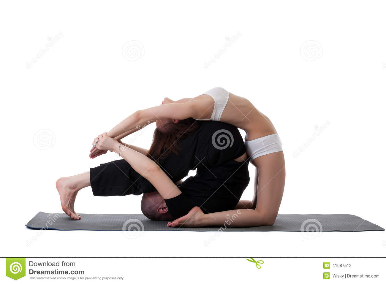 Side view of healthy couple doing yoga in studio