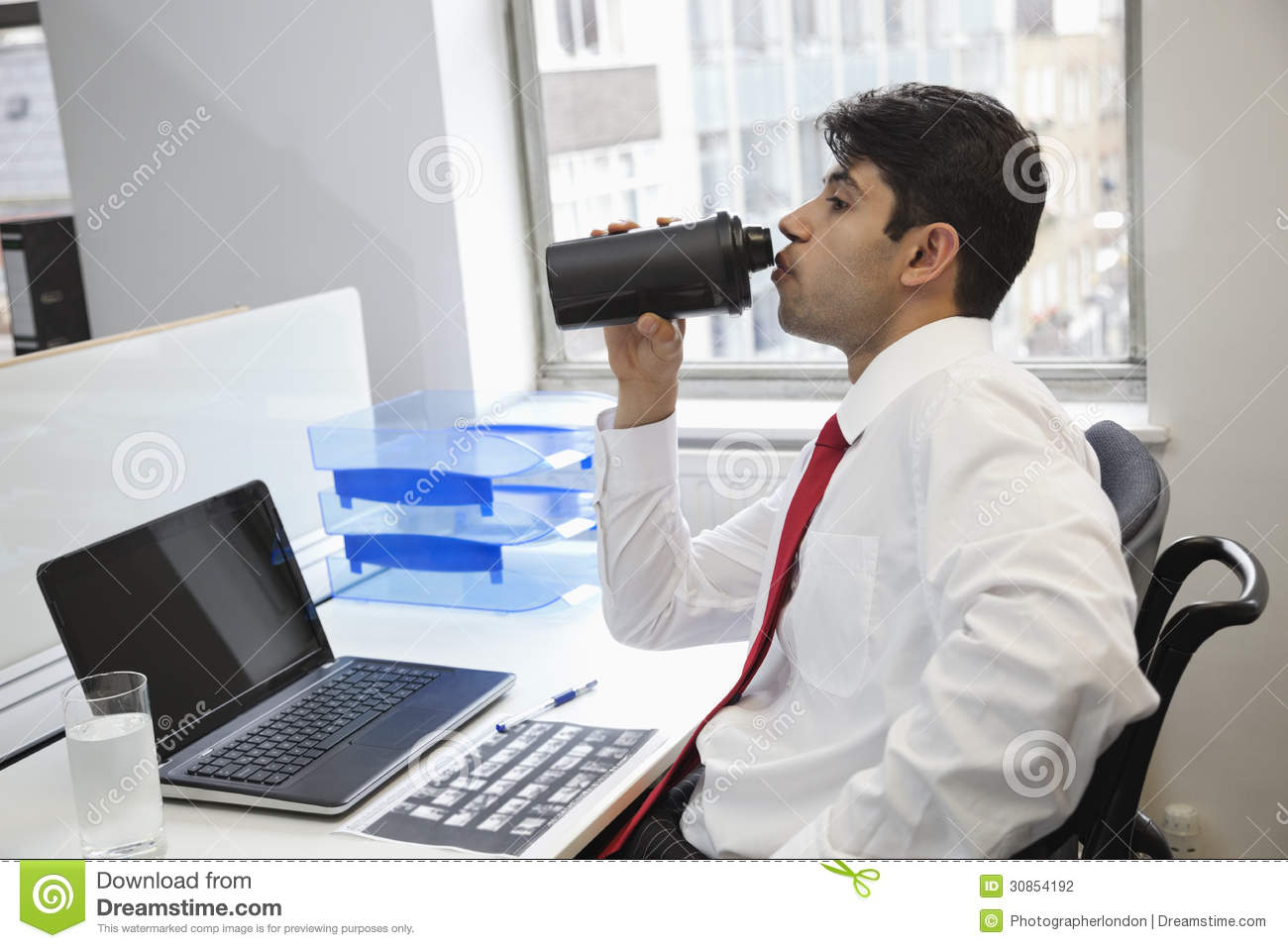 Side View Of An Indian Businessman Drinking Water At Office Desk Stock Photo Image